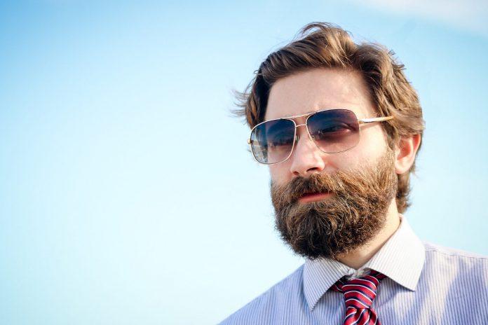 Mężczyzna z brodą w okularach przeciwsłonecznych w koszuli i krawacie