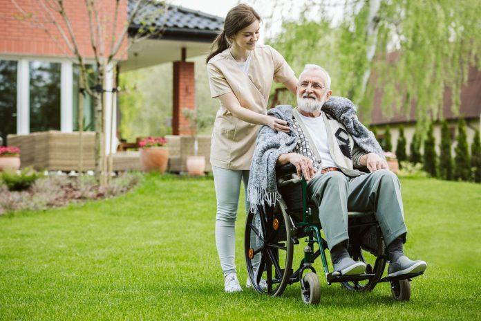 Starsza osoba na wózku z opiekunką